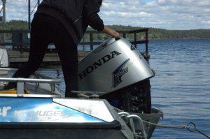 plockar av motorkåpan på båten